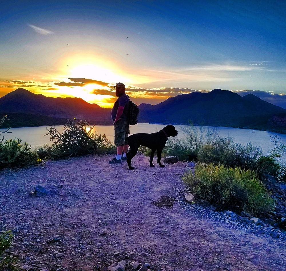 Hiking Butcher Jones Trail  - Hiker and dog at sunset over the lake, on the Butcher Jones Trail at Saguaro Lake, Arizona
